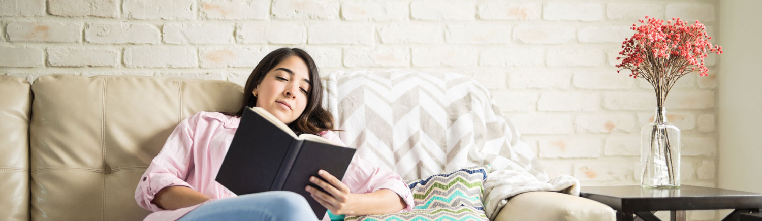 Girl reading a book sitting on a sofa